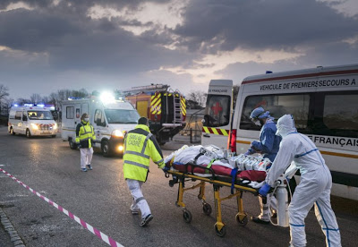 Emergency medical personnel carries a patient affected with coronavirus from a military hospital to an ambulance. Photo: AFP